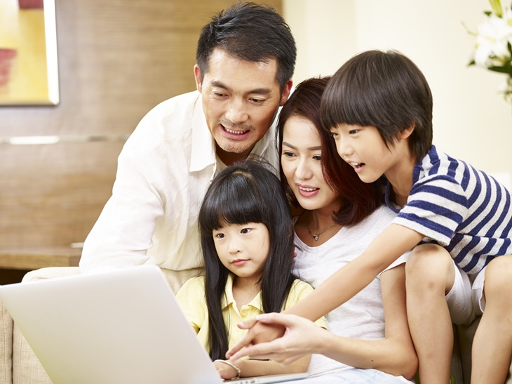 asian family using laptop computer together at home
